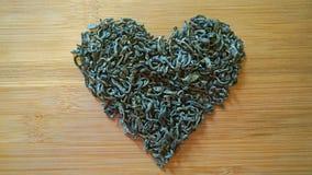 心脏由绿茶制成在木竹纹理 免版税库存图片