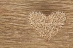 心脏由饰以珠宝的亚麻布制成在橡木板背景  库存图片