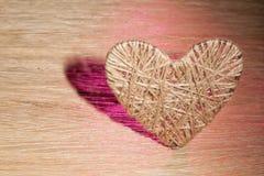 心脏由饰以珠宝的亚麻布制成在橡木板背景  免版税图库摄影
