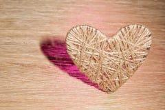 心脏由饰以珠宝的亚麻布制成在橡木板背景  免版税库存图片