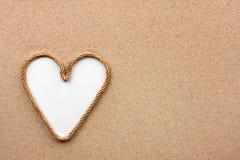 心脏由绳索制成有白色背景在沙子 库存照片