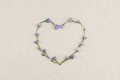 心脏由紫色切削刀做的形状框架开花 免版税库存照片