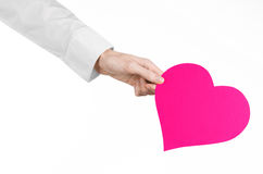 心脏病和健康题目:递拿着卡片的一件白色衬衣的医生以桃红色心脏的形式被隔绝 免版税库存图片