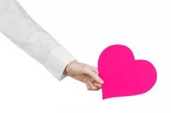 心脏病和健康题目:递拿着卡片的一件白色衬衣的医生以桃红色心脏的形式被隔绝 图库摄影