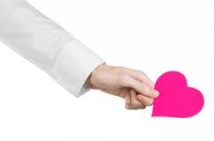 心脏病和健康题目:递拿着卡片的一件白色衬衣的医生以桃红色心脏的形式被隔绝 库存照片