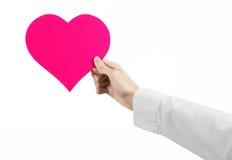 心脏病和健康题目:递拿着卡片的一件白色衬衣的医生以桃红色心脏的形式被隔绝 免版税图库摄影