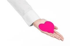 心脏病和健康题目:递拿着卡片的一件白色衬衣的医生以桃红色心脏的形式被隔绝 免版税库存照片