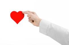 心脏病和健康题目:递拿着卡片的一件白色衬衣的医生以红色心脏的形式被隔绝 库存图片