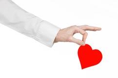 心脏病和健康题目:递拿着卡片的一件白色衬衣的医生以红色心脏的形式被隔绝 免版税库存照片