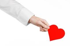 心脏病和健康题目:递拿着卡片的一件白色衬衣的医生以红色心脏的形式被隔绝 图库摄影