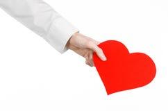 心脏病和健康题目:递拿着卡片的一件白色衬衣的医生以红色心脏的形式被隔绝 免版税库存图片