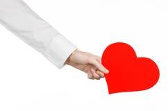 心脏病和健康题目:递拿着卡片的一件白色衬衣的医生以红色心脏的形式被隔绝 免版税图库摄影