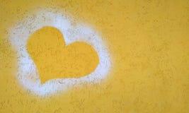 心脏的剪影在黄色膏药墙壁上的 免版税库存图片