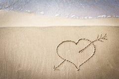 心脏的图画在沙子的在海景背景 免版税库存图片