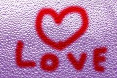 心脏的图象和在一个湿misted窗口的一个问号 Emo 免版税图库摄影