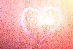 心脏的图象和在一个湿misted窗口的一个问号 Emo 库存照片