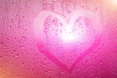 心脏的图象和在一个湿misted窗口的一个问号 Emo 库存图片