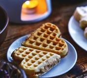 以心脏的形式两个薄酥饼蛋糕在一张服务的木桌上的一块小板材说谎 免版税图库摄影