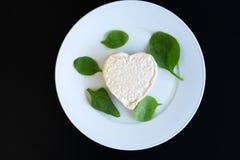 以心脏的形式乳酪在一块白色板材 库存照片