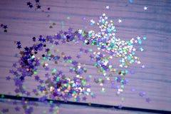 以心脏的形式五颜六色的五彩纸屑在紫色背景前面 免版税库存照片