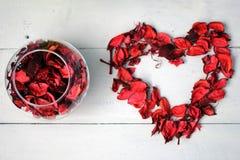 以心脏的形式图和一个碗玫瑰花瓣 免版税库存照片