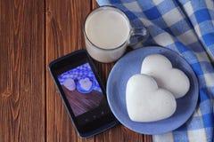 以心脏的形式姜饼干在茶碟、一个在一张木桌上的杯子热巧克力和smarfon 库存照片