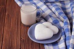 以心脏的形式姜饼干在茶碟和一个杯子在一张木桌上的热巧克力 库存照片