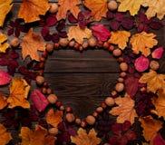 以心脏的形式平的位置框架从秋天绯红色和ye 免版税库存照片