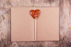 以心脏的形式棒棒糖和与空白页的一本老日志 图库摄影