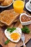 以心脏的形式煎蛋在木板,顶视图 免版税库存图片