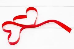 以心脏的形式红色丝带在白色木背景 图库摄影