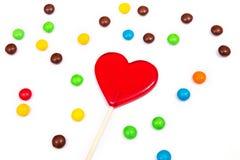 以心脏的形式红色棒棒糖用在白色背景的五颜六色的按钮型巧克力 免版税图库摄影