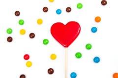 以心脏的形式红色棒棒糖用在白色背景的五颜六色的按钮型巧克力 免版税库存图片