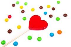 以心脏的形式红色棒棒糖用在白色背景的五颜六色的按钮型巧克力 库存图片