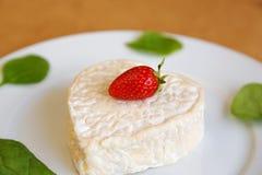 以心脏的形式草莓乳酪在一块白色板材 库存图片