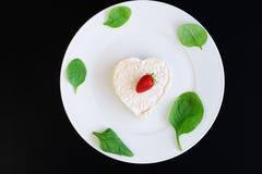 以心脏的形式草莓乳酪在一块白色板材 免版税库存照片