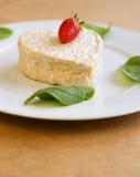以心脏的形式草莓乳酪在一块白色板材 免版税库存图片