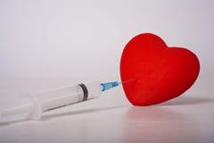 以心脏的形式被放置的注射器 库存照片