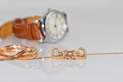 以心脏的形式金耳环在背景典雅 免版税库存照片