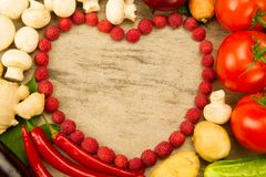 心脏的菜形状在木背景,素食食物的 健康的饮食 库存图片
