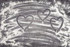 心脏绘与在麦子膳食的手指一个灰色加工面上 免版税库存照片