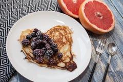 心脏薄煎饼用在一块白色板材的黑莓 背景用葡萄柚 浪漫或健康早餐 库存照片