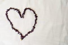 心脏被计划女性美丽的小珠,棕色黑暗的石头项链,琥珀色反对米黄织品背景  免版税库存照片