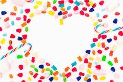 心脏被隔绝的由色的明亮的糖果制成在白色背景 平的位置,顶视图 库存图片