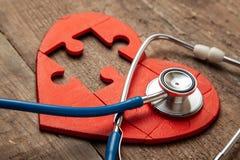 心脏难题红色和听诊器在木背景 概念心脏病,医疗保险的诊断和治疗 库存照片