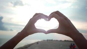 心脏,爱,海滩的女孩递显示心脏,日落,并且海能通过妇女的被看见 股票视频