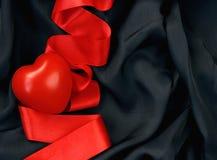 心脏,红色缎丝带,黑丝绸 库存图片