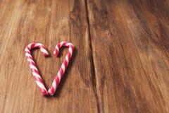 心脏以纪念华伦泰由棒棒糖做的` s天在老木板条背景  免版税库存图片