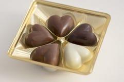 心脏shapped巧克力甜点,棕色和白色颜色,透明塑料盒用果仁糖 库存图片
