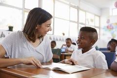 志愿他的书桌的老师帮助的男小学生,关闭  免版税图库摄影